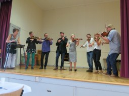 faculty playing a concert set. including teachers for the singing class, the dance class, and the blacksmithing class.