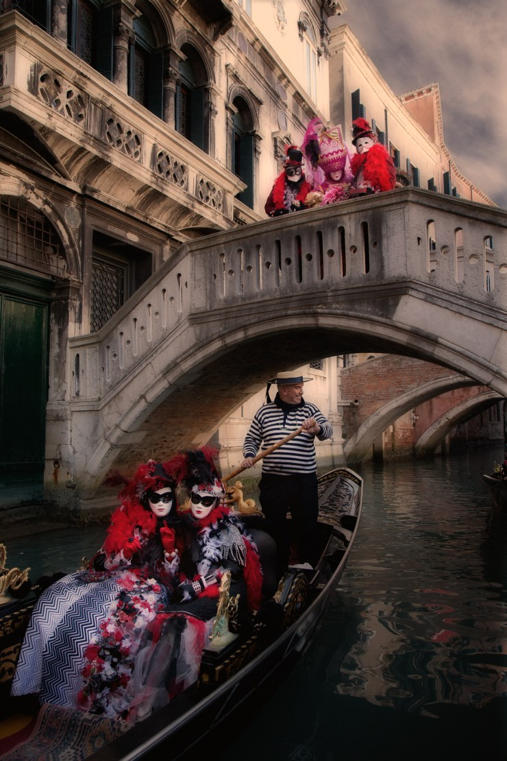 Carnival models riding in a gondola on a Venice canal