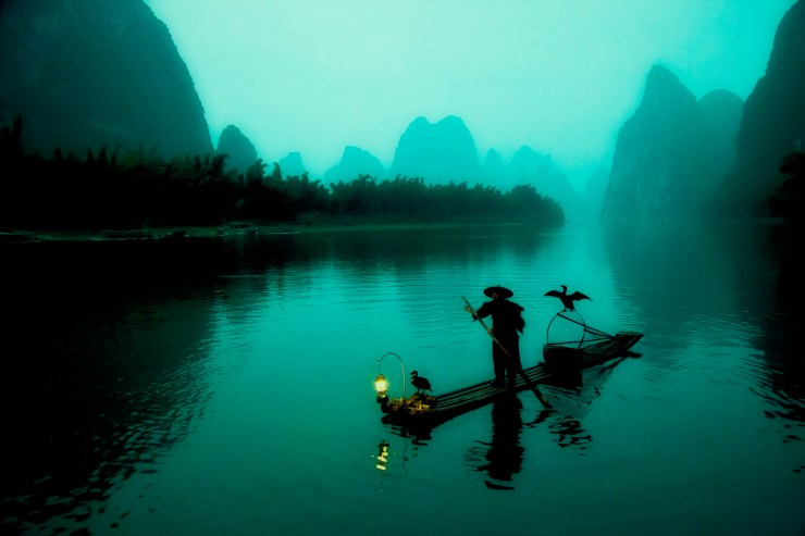 Chinese fisherman silhouette on the Li River in the early morning. To get to this spot, you need to take a boat up the Li River in complete darkness, which is a surreal experience.