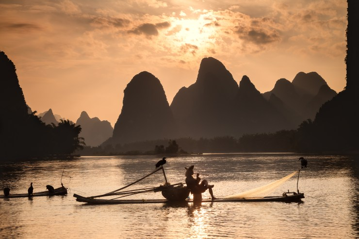 A fisherman on the Li River at Xingping near Guilin taking a break. This was my fourth attempt at good lighting with the cormorant fishermen. This sunrise made it all worth it.