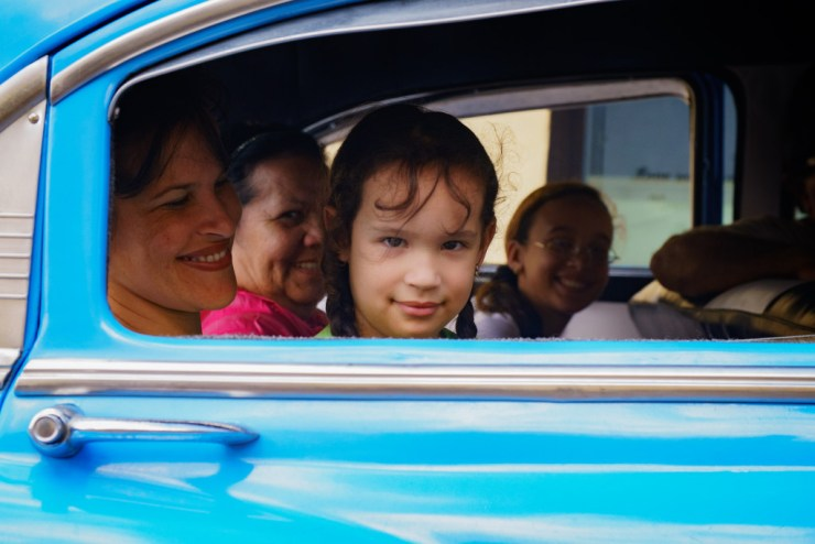 A girl peers out of her family vehicle in Holguin. Photographed with a Tamron 24-70 f/2.8 at 1/1250 and f/4.5.