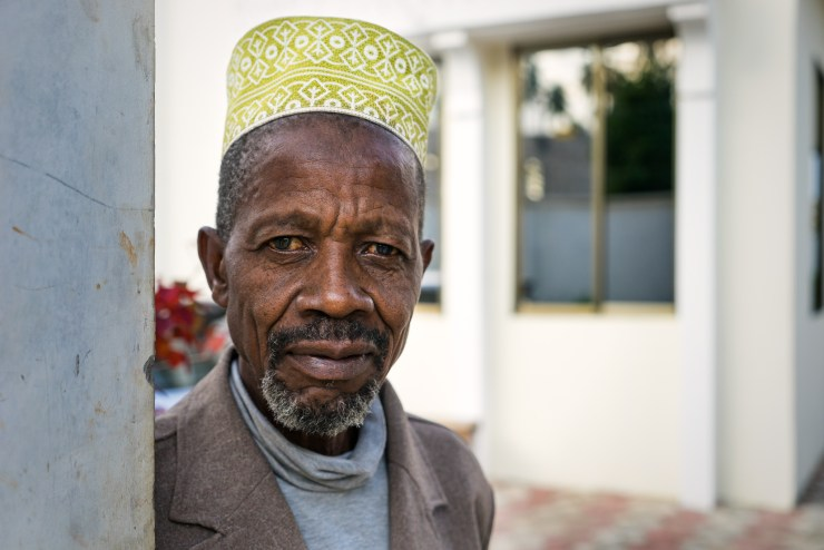 "This is Babu. Babu means ""grandfather"" in Swahili. He's the sweetest man. He is the caretaker at Art in Tanzania's volunteer house in Fuoni. He is the kind of man who doesn't speak much but has a benevolent gaze and a face that tells many stories. Babu always wears a Bargashia, Zanzibar's variant of the Kofia, the traditional hat worn by men in East Africa, especially by Swahili-speaking people."
