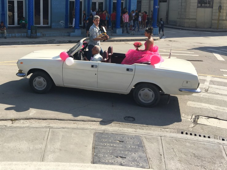 A convertible travels around the Parque Central of Holguin to celebrate the Quinceañera (15th Birthday) of a local young woman.