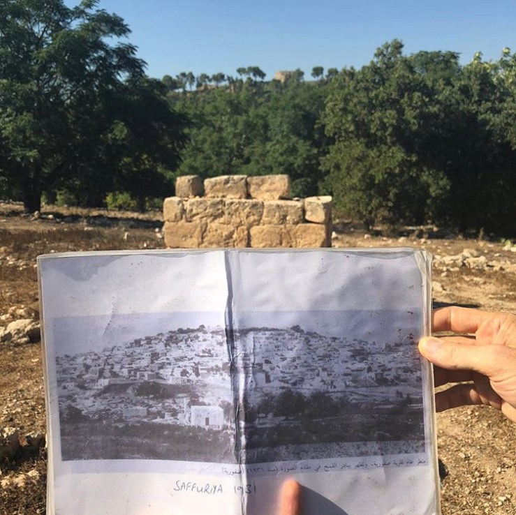 A picture of the fields where a demolished village lay, with a book in front with a picture of the village as it looked in 1931
