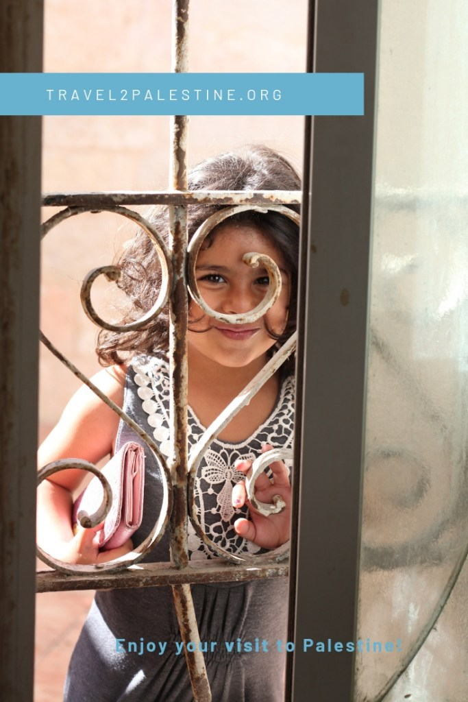 A Palestinian child looking through a window