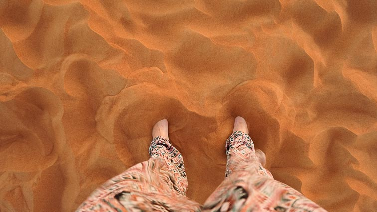 Kir's feet in the desert sand in Dubai. How expensive is Dubai?