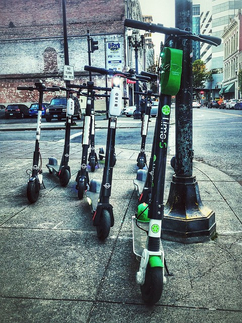 several electric-powered scooters parked on a street corner