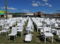 """""""185 square meters of grass depicting new growth, regeneration. 185 white chairs, all painted twice by hand as an act of remembrance. This installation is temporary - as is life."""" - Pete Majendie"""