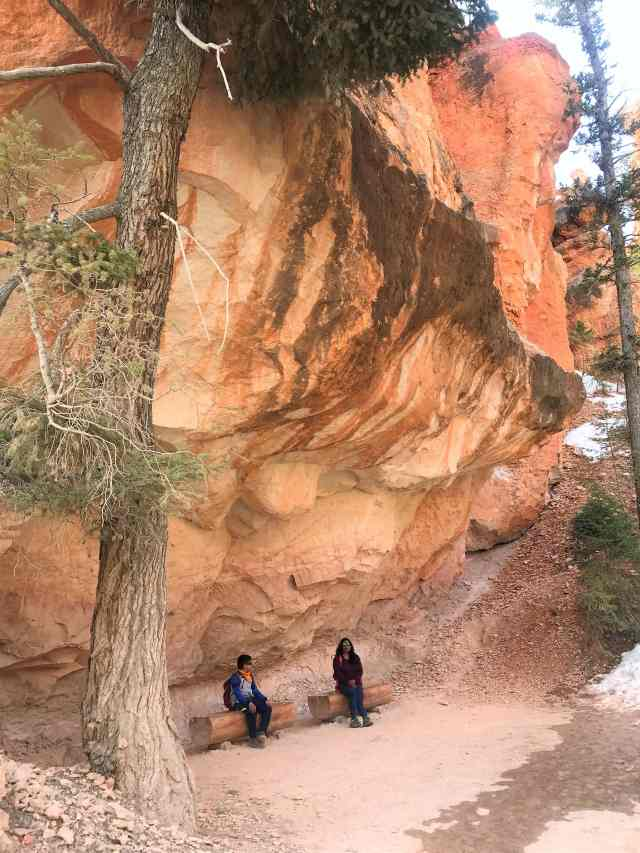 Taking some break on the Wooden Log under the massive huge rock on  Peek-A-Boo Loop Trail.  Best Hikes in Bryce Canyon National Park