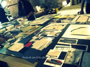 Laying out the pictures of furniture, fabric before gluing them onto the mood board.