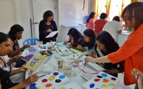 Art workshop held at West Coast women's labour camp in Mussafah, Abu Dhabi, on May 10, 2013, led by artist Nirina Ralanto (standing left) and co-led by Michal Teague, artist and coordinator of Labor of Love's 'Camp Creative' initiative (standing right).