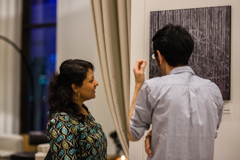 Onishi and I have a discussion on mixed media art and especially the application of black hot glue onto canvas. Photo by CurlyWurlyPhotography. Rights with Vida DowntownDubai. Used with permission.