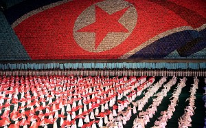 "North Korean women dance in front of a display of their country's national flag on Monday, July 22, 2013 in Pyongyang, North Korea. North Korea has revealed a new rendition of the ""Arirang"" mass games, the song-and-dance ensemble. This year's performance was timed to debut for the 60th anniversary Saturday of the end of the Korean War, and features new scenes focusing on leader Kim Jong Un's directives. (AP Photo/Wong Maye-E)"