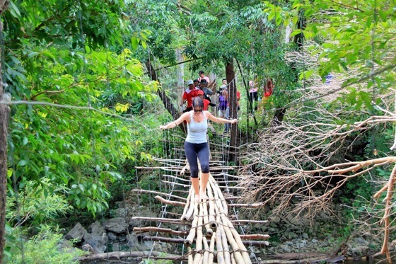 Sweaty messy Clelia trying to cross a bamboo bridge in The Philippines with Clelia Mattana or Kle from Keep Calm and Travel
