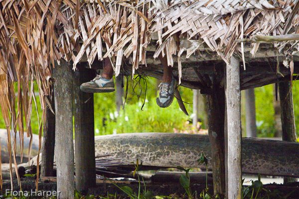 Feet dangle below Longhouse, Kopar village, Sepik River, Papua New Guinea Photo Fiona Harper travel writer