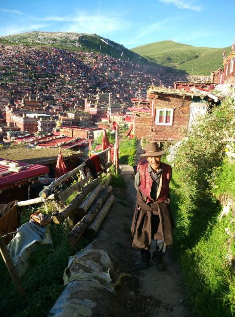 עולה רגל טיבטי הולך בשבילים בין צריפי הנזירים (צילום: חיים קלאי)