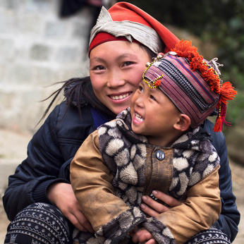 Happy Hmong woman and child smiling, sitting outside their house at Giang Ta Chai village near the hill town of Sa Pa, Lao Cai Province, North Vietnam.