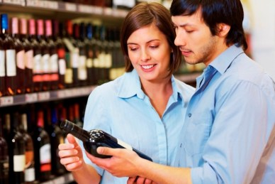 Young couple checking out for a wine bottle to purchase