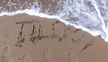 Tilos scritto sulla sabbia di una spiaggia