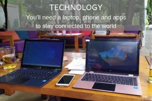 Things to Consider as a Digital Nomad - Technology. 2 laptops and a phone on a table in an outdoor restarurant