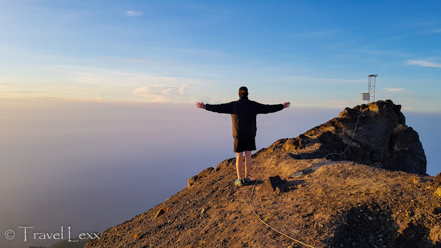 A person standing at the rim of Mt Merapi volcano with big drops on either side