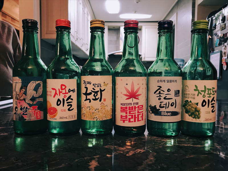 Six glass bottles with colourful labels lined up on a kitchen counter