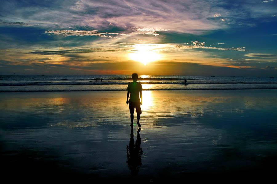 A child watching a sunset at a beach