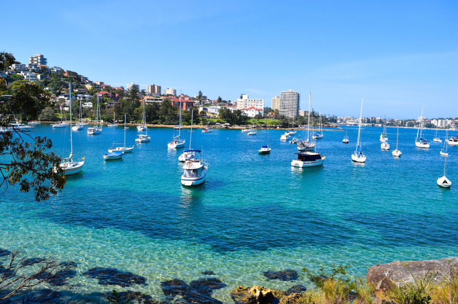 Boats moored in a bay with crystal clear water along the hike from Manly beach to Spit Bridge in Sydney, Australia