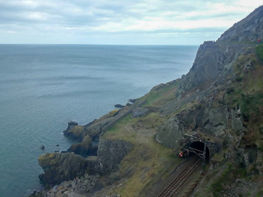 A train track entering a tunnel above the sea between Bray and Greystones in Ireland