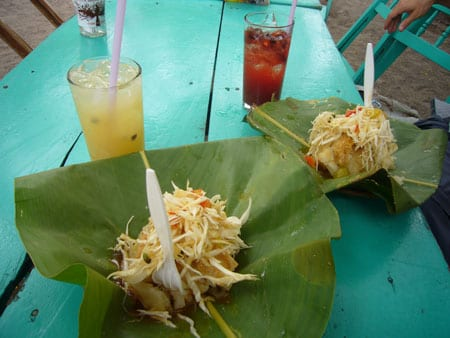 Yuca Vigorón served in a banana leaf, cabbage and pork rind
