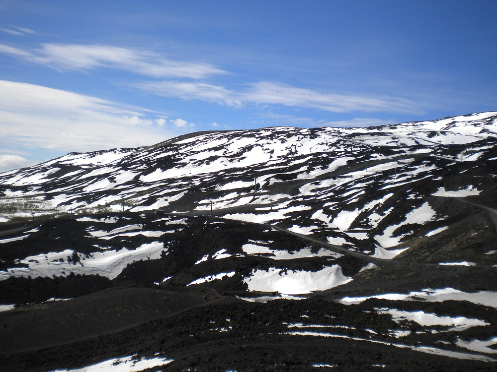 Black lava, white snow and blue sky, the pure colors of Mount Etna