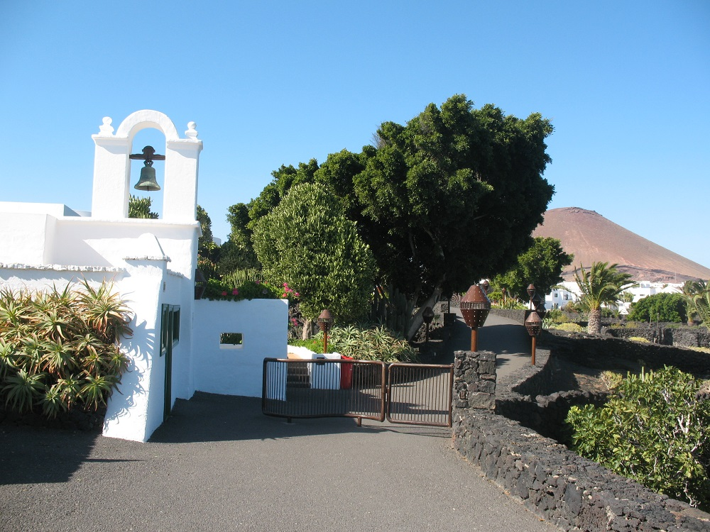 The alley leading to the entrance to Fundacion Cesar Manrique in Lanzarote with a volcanic cone in the background.