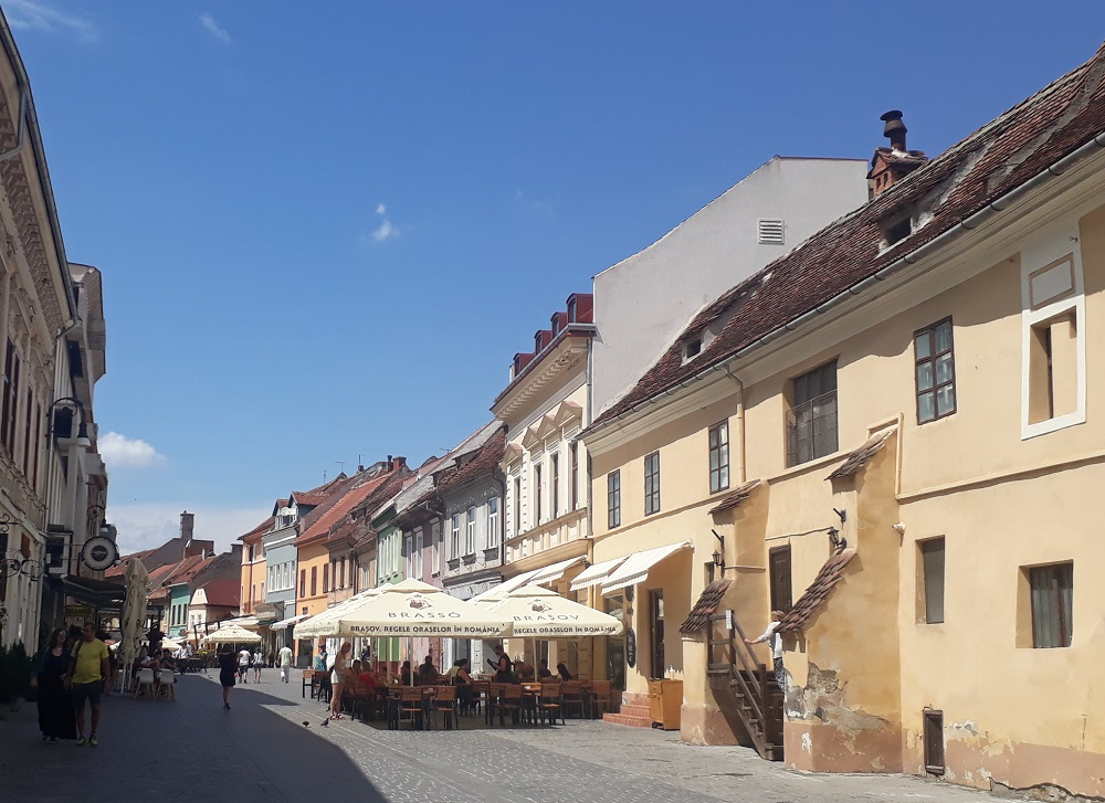 Pedestrian street with traditional houses and outside terraces in the center of Brasov.