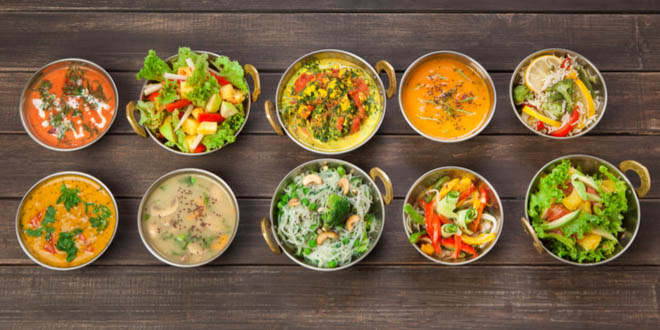 Selection of Indian vegan dishes such as hot spicy indian soups, rice and salads in copper bowls.