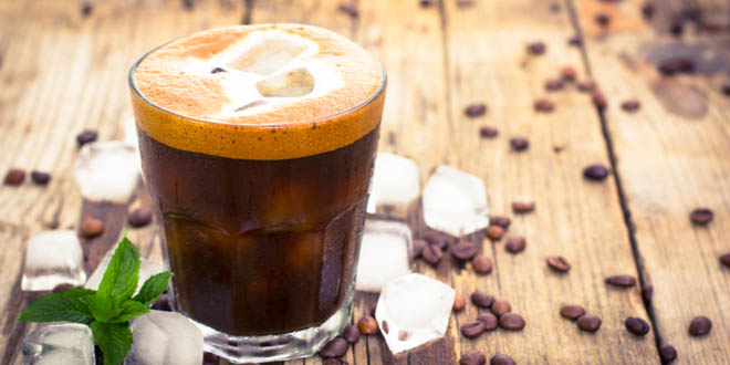 Ice coffee in a glass on a wooden table, one of the typical Cypriot desserts