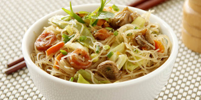 Fried Pancit bihon noodles, one of the best-known filipino foods, served on a bowl with chopstick