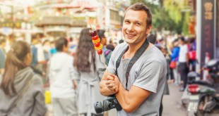 Man posing with a camera for taking amazing food pictures when travelling.