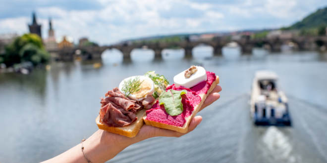 Hand holding must-try foods in Prague, with the river on the background.