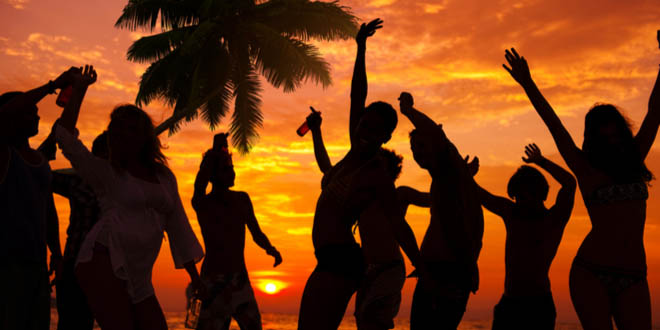 Silhouettes of people partying on a Caribbean beach with Stripe, the best Jamaican beer.
