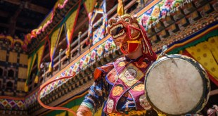 Buddhist monk dancing with a dragon mask at Paro Tsechu festival in Bhutan, a great ocassion for trying typical Bhutanese dishes.