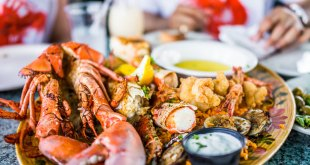 Close-up of lobsters and seafood on a plate with tartar sauce in one of the best seafood restaurants in Florida.