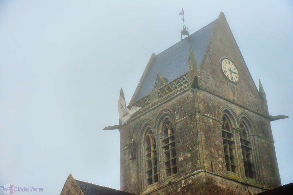 Closeup of parachute hanging off church tower of Sainte-Mere-Eglise in Normandy