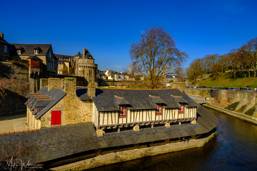 Old wooden houses (stables?) alongside the river stream running through the gardens of the ramparts in Vannes in Brittany