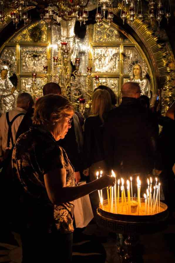 Lighting a candle inside the Church of the Holy Sepulchre