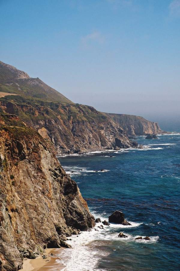 The sawtoothed California coastline at Big Sur, an essential stop on a Pacific Coast Highway road trip