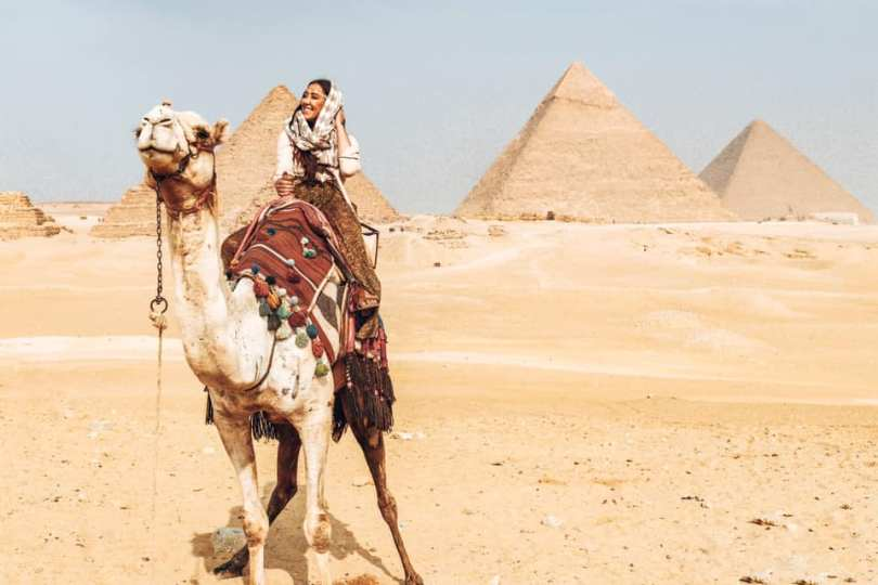 Emily Rose riding a camel in front o the Pyramids of Egypt.