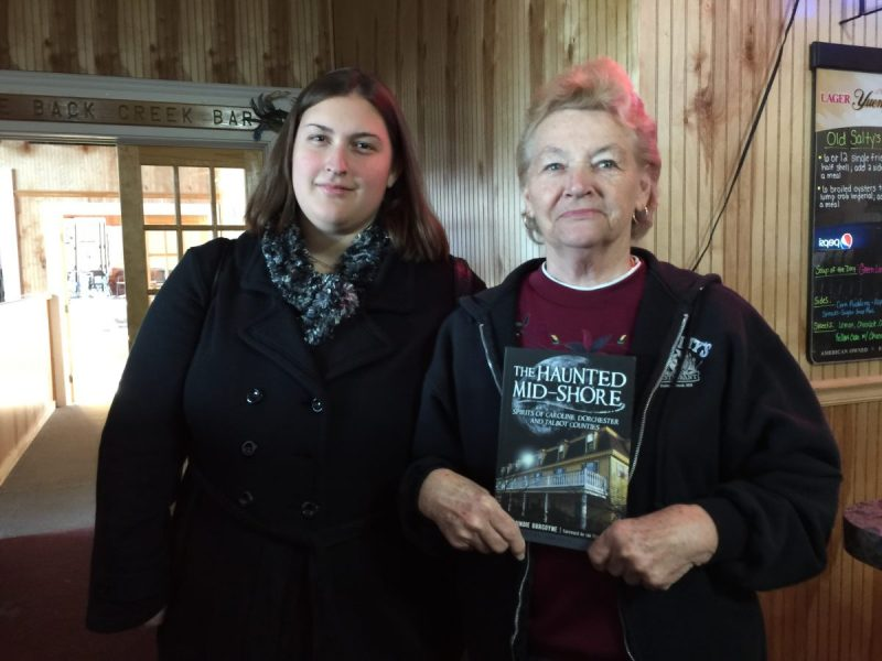 "Mary, from Hoopers Island and her granddaughter, holds the book where her story, ""Mary's Ghost"" is featured."
