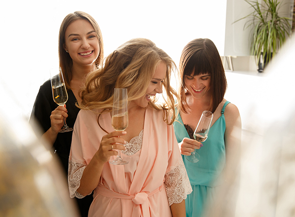 Cheerful girls drinking champagne at the bridal shower, at home