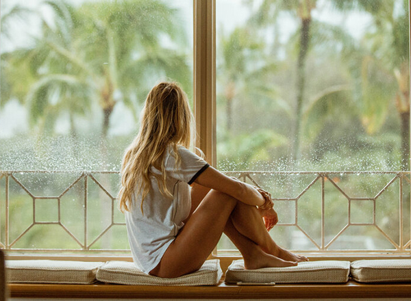 Woman looking out of window in the tropics