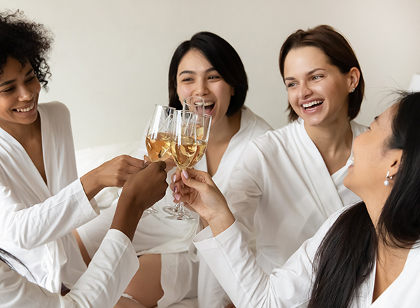 Happy multiethnic young women wear bathrobes clink glasses on bed